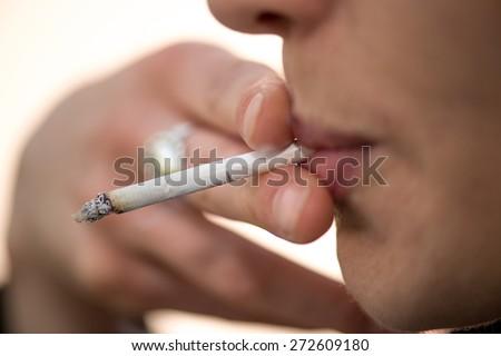 Woman smoking slim cigarette closeup - stock photo