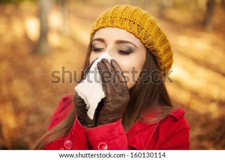 Woman sneezing in handkerchief at autumn  - stock photo