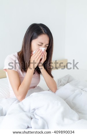 Woman sneezing in her bed - stock photo