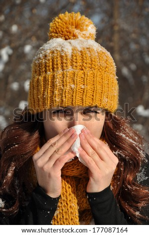 Woman sneezing into tissue, winter outdoor portrait - stock photo