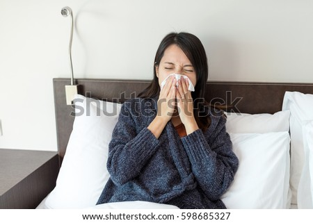 Woman sneezing on bed