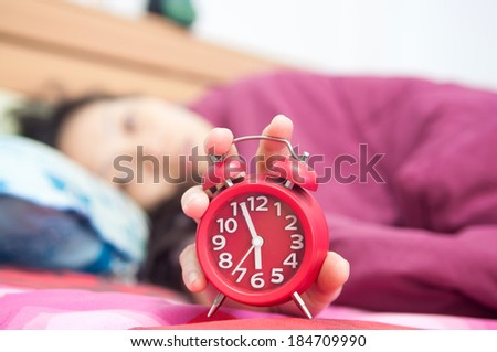 Woman snoozing a red alarm clock - stock photo