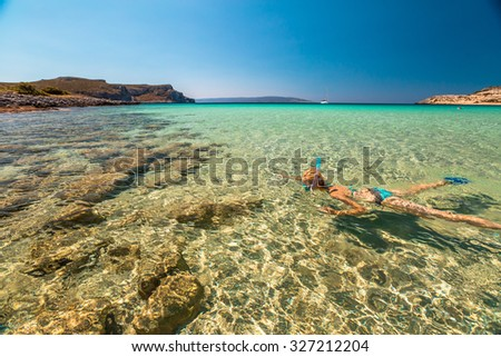 Woman snorkeling in beautiful blue waters of the famous Simos Beach, Elafonisos, Greek version of the Maldives, the most exotic island in Mediterranean , Peloponnese, Greece.