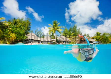 Woman snorkeling in clear tropical waters in front of exotic island - stock photo