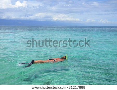 Woman snorkeling in crystal clear water