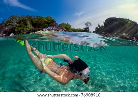 Woman snorkeling in front of tropical island