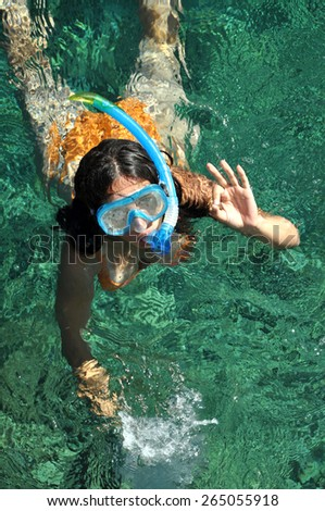 Woman snorkeling in the sea and doing the ok sign - stock photo