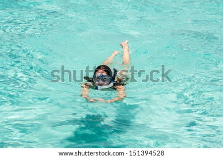 woman snorkeling in tropical water - stock photo
