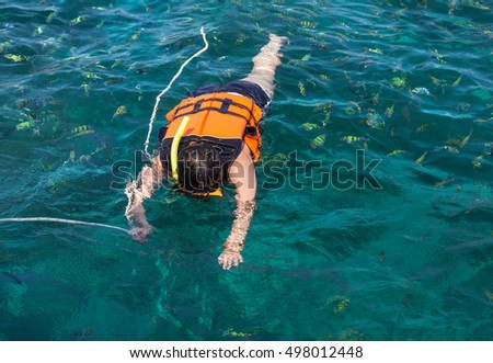 woman snorkeling with life jackets in andaman sea at phi phi islands, Thailand