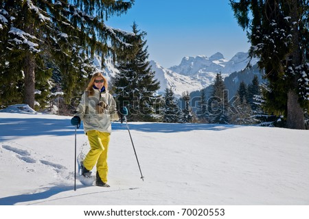 Woman snow-shoeing in the Alps - stock photo