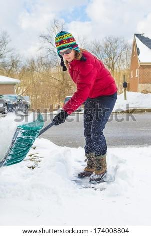 Woman Snow Shoveling Driveway - stock photo