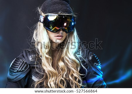 Woman Snowboarder in the mask and helmet on a black background