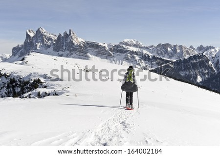 Woman snowshoeing along mount peak against Dolomites - stock photo