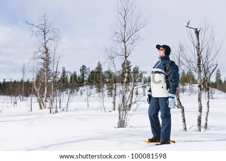 Woman snowshoeing in the wildlife and enjoying the sun.