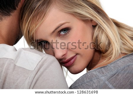 Woman snuggling up to her husband - stock photo