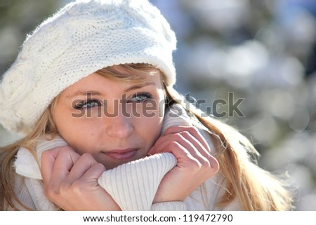 Woman snuggling up to her warm clothing - stock photo