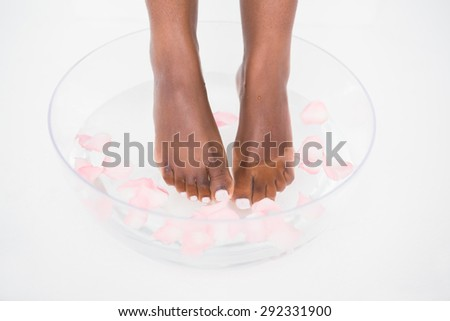 Woman soaking her foot in a transparent bowl - stock photo