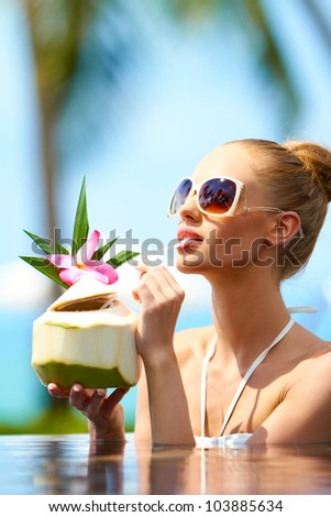 Woman soaking in a pool in her bikini and sunglasses sipping a tropical cocktail through a straw - stock photo