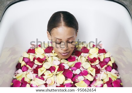 Woman soaking in bathtub filled with rose pedals - stock photo