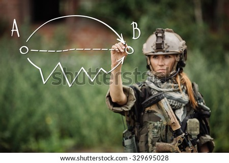 woman soldier writes marker on transparent glass  - stock photo