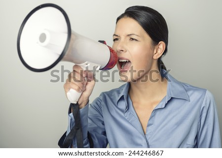 Woman speaking over a megaphone as she makes a public address, participates in a protest or organises a rally or promotion, over grey with copyspace to the side