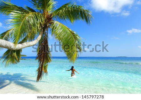 Woman splashing in sea near beautiful beach with palm - stock photo