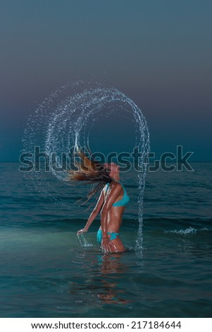 Woman splashing water with her hair in the ocean at night