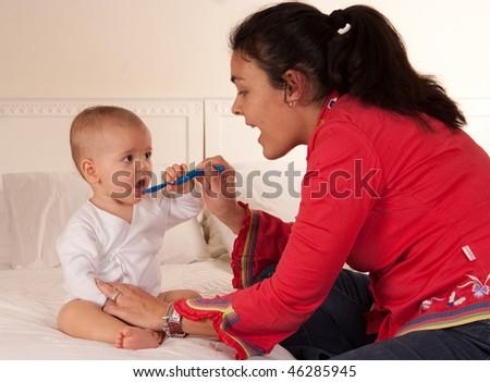 Woman spoon feeding her baby - stock photo