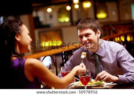 Woman spoon-feeds her boyfriend in the restaurant - stock photo