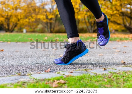 Woman sport running through autumn or fall park