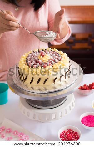 Woman sprinkling icing sugar over cake - stock photo