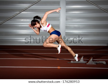 Woman sprinter leaps from starting block.