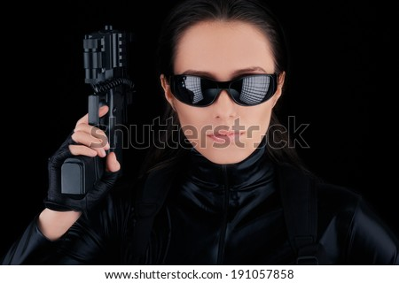 Woman Spy Holding Gun - Woman in a black leather suit holding a gun   - stock photo