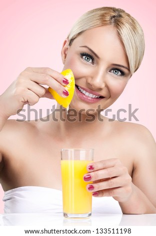 Woman  squeezes the juice from the lemon in glass - stock photo