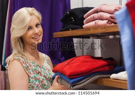Woman stacking shelf in clthing store and smiling - stock photo