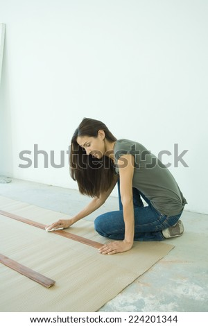 Woman staining slats of wood - stock photo