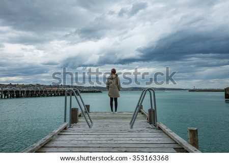 woman stand alone at the edge of the bridge - stock photo