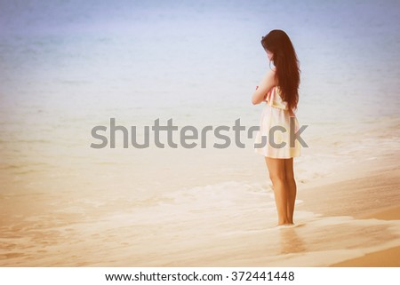 Woman stand alone, lonely On the beach Staring at the Sea style vintage Tone. - stock photo