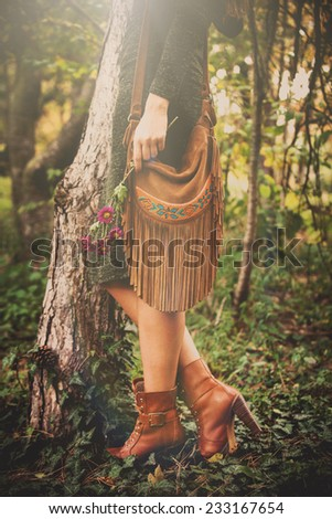 woman stand by the tree hold flowers in hand wearing leather handbag, green dress and brown ankle boots, retro colors - stock photo