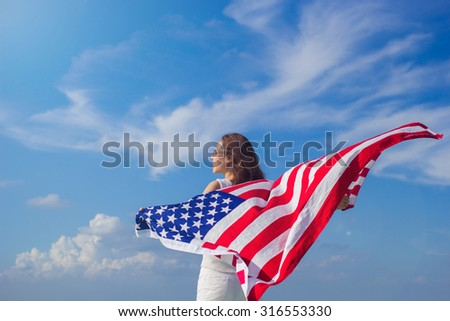 woman stand facing the sky her hands holding America flag.freedom concept,happy labor day,independence day.patriotic concept.citizenship day.soft focus:freedom:i have a dream campaign of MLK's Day. - stock photo