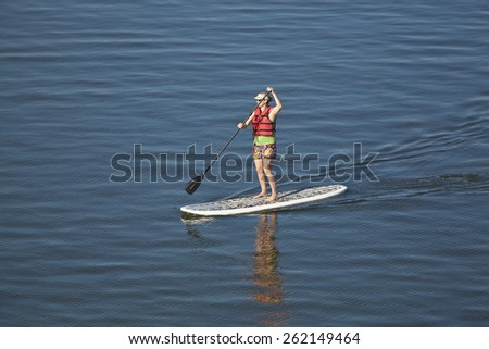 Woman stand up paddleboarding on open water - stock photo