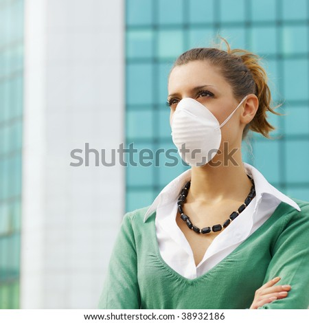 woman standing against office building and wearing protective mask. Copy space - stock photo