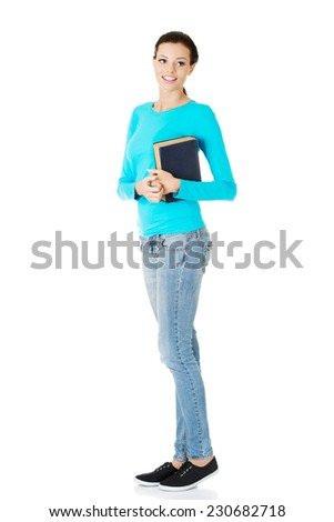 Woman standing and holding a book. - stock photo