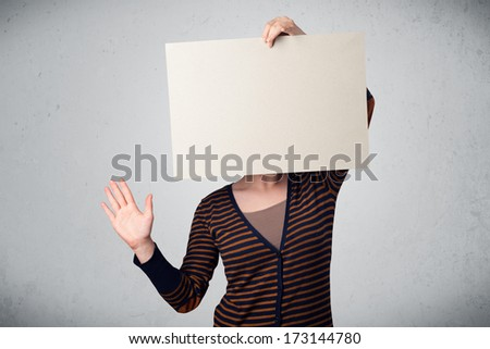 Woman standing and holding in front of her head a white paper with copy space