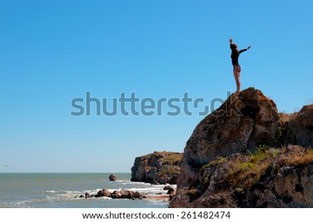 Woman standing and relaxing on a natural coastal rock high up, contemplating the sea against a blue sky. Well being healthy lifestyle - stock photo