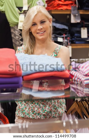 Woman standing at a clothes rack in a boutique smiling