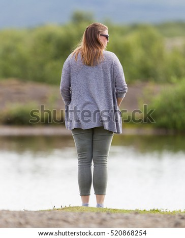 Woman standing at a riverside in Iceland