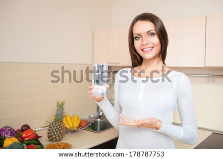 woman standing at kitchen and holding glass with fresh water