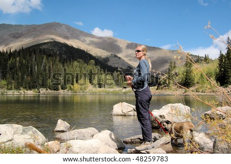 Woman standing at lake with dog