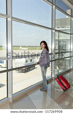Woman standing  at the airport window. - stock photo